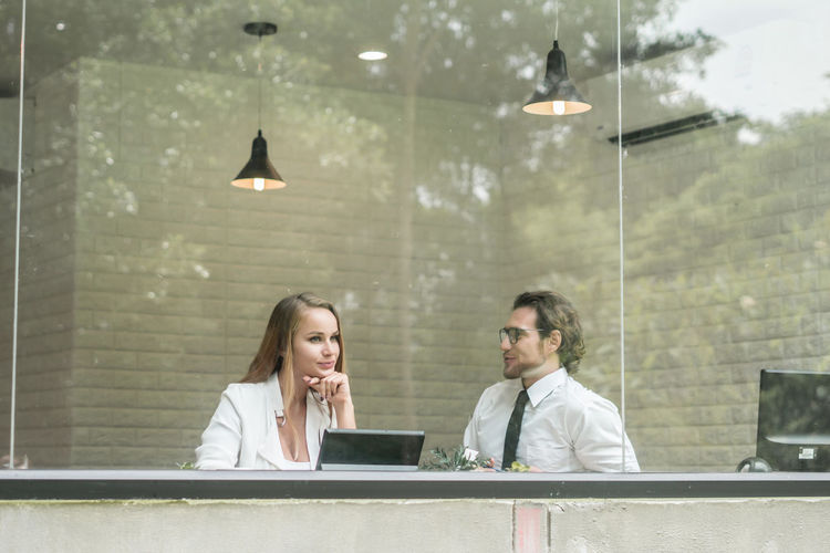 Business Colleagues Discussing While Sitting In Office Seen Through Window
