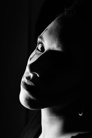 Portrait of thoughtful young woman against black background