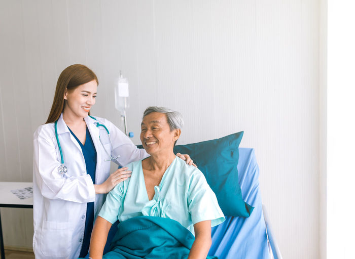 Female Doctor With Smiling Senior Male Patient On Bed In Hospital