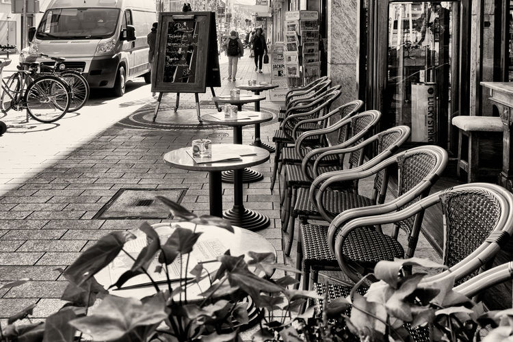 MANNHEIM, GERMANY - April 10, 2017: Tables with chairs infront of a cafe in downtown invite for a breakfast or a coffee Transportation Bicycle Mode Of Transportation Street Footpath City Day Land Vehicle Sidewalk No People Architecture Building Exterior Outdoors Seat Large Group Of Objects Business Nature Garbage Built Structure Wheel