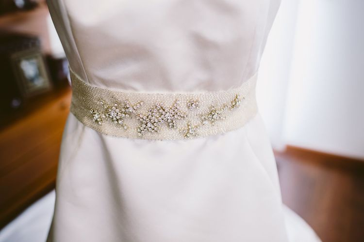 Midsection of bride wearing wedding dress at home